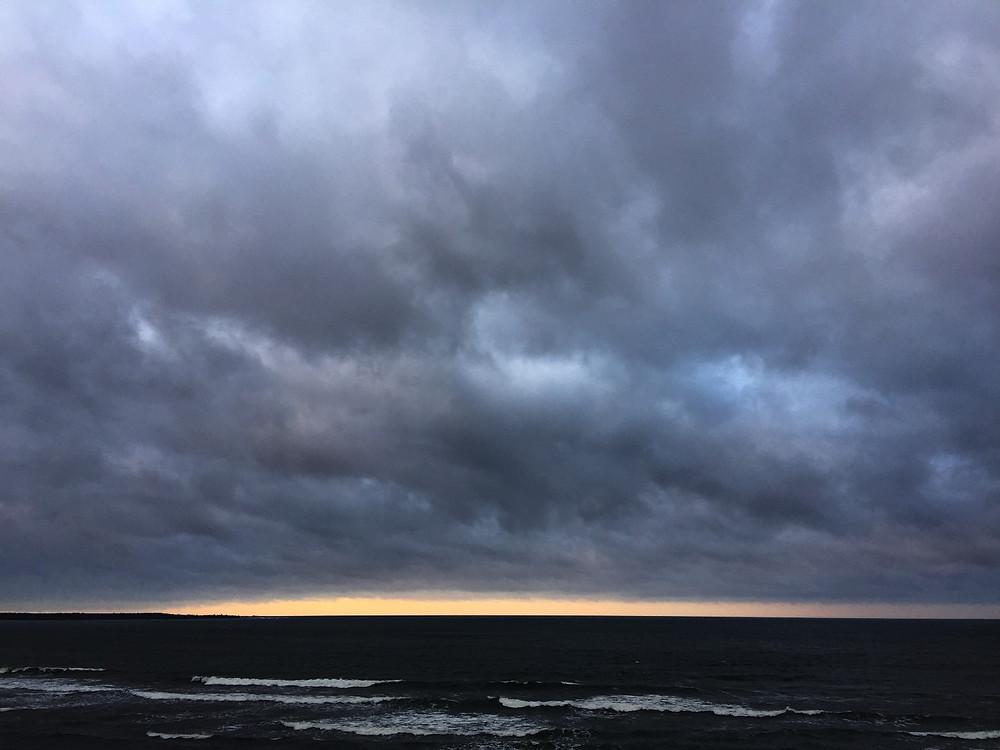 The sun valiantly peaks through the black clouds near Palidski, Estonia.