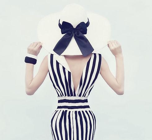 Dame mit Schwarz-Weißen Kleid und Weißem Hut mit breiter Krempe und schwarzem Band