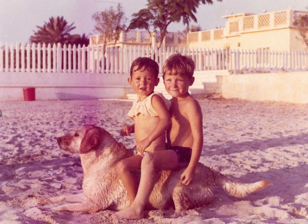 My sister and I sitting on Cindy the dog at the King of Bahrain's beach residence in Bahrain, 1969