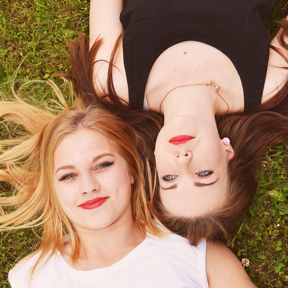two woman laying in grass beautiful hair by victoria salon