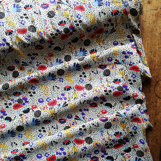 Viscose dressmaking fabric with an abstract geometric floral design  on a pale background