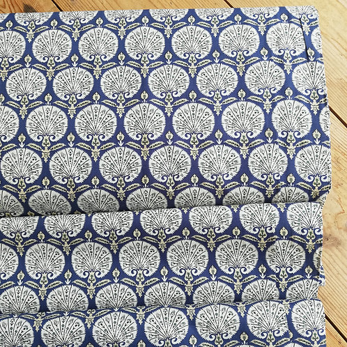 Pima cotton lawn dressmaking fabric with a shell motif on a blue background