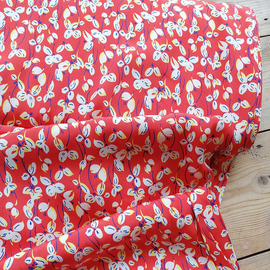 Viscose crepe dressmaking fabric with little leaves in white with hints of yellow and blue on an orange background