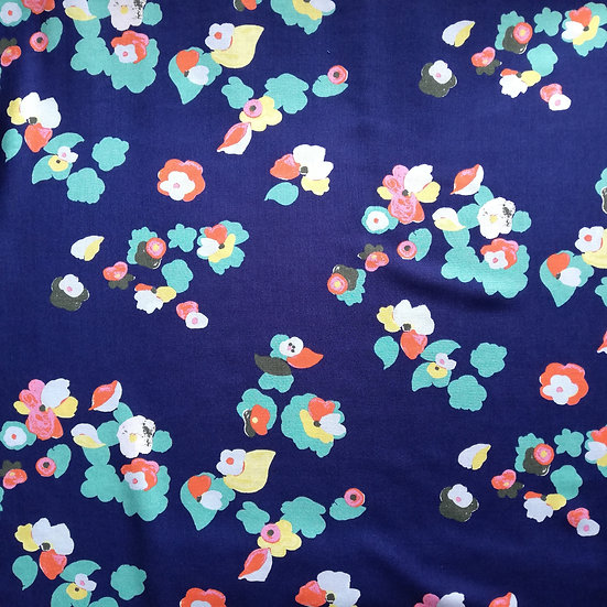 Polyester vintage inspired floral dressmaking fabric on a dark blue background