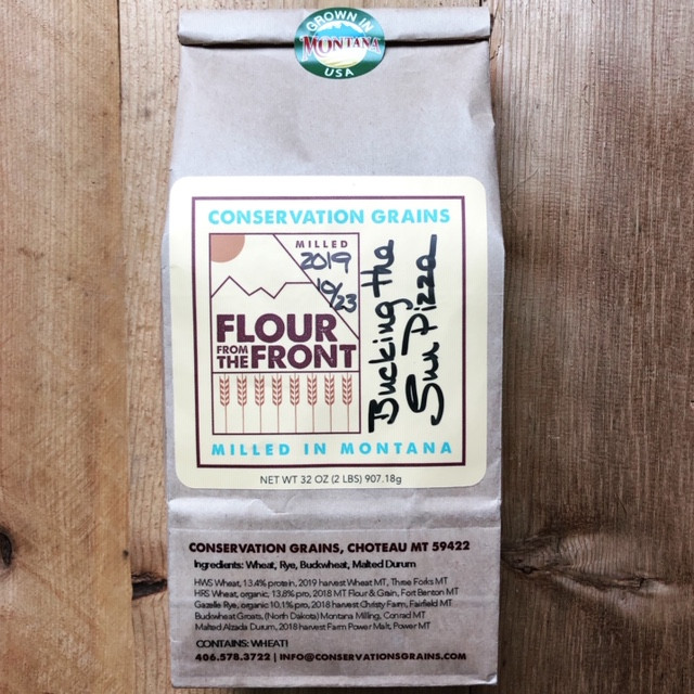 small brown flour bag with yellow, blue, and red label. brown and grey wood background.