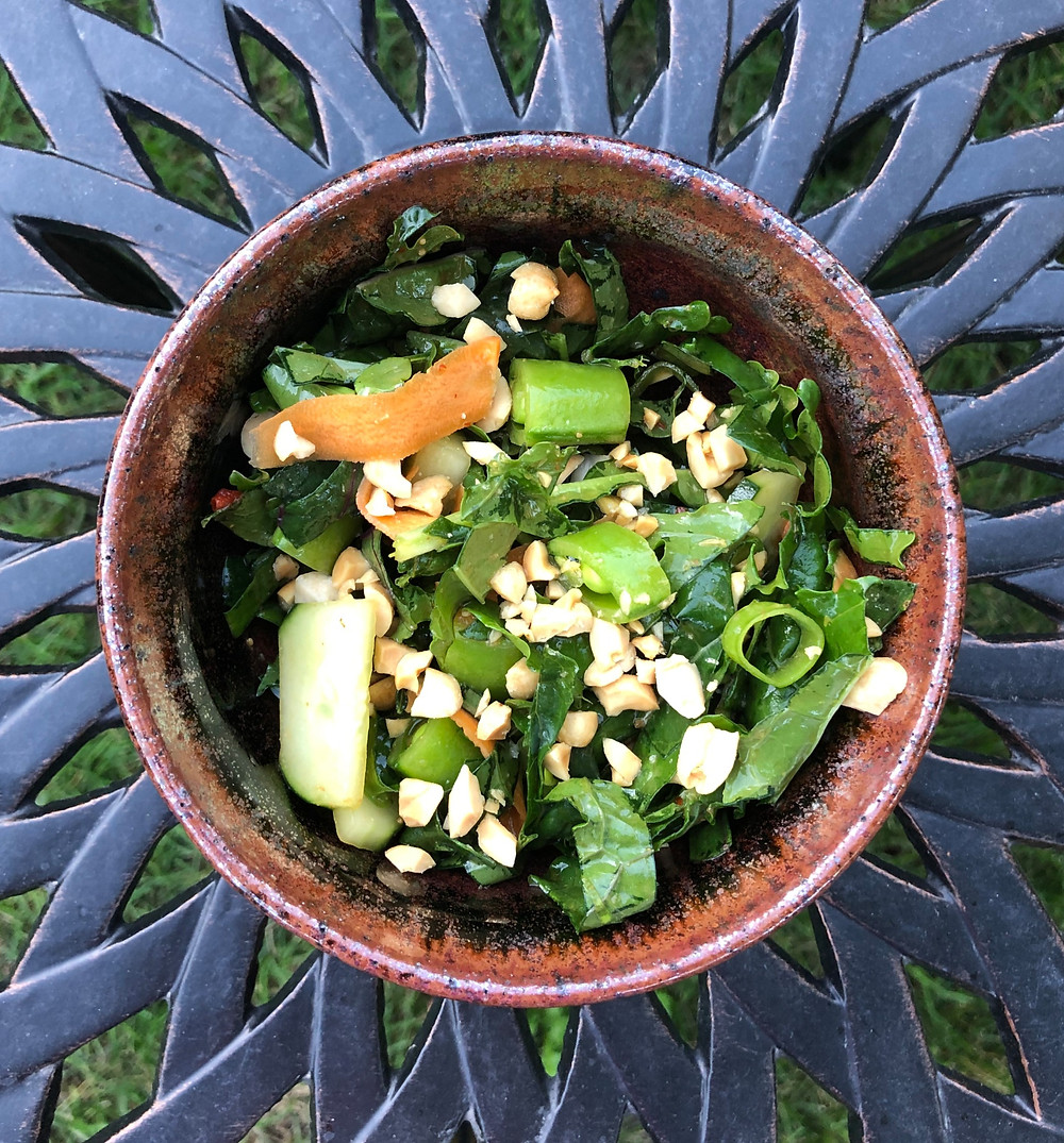 brown pottery bowl with green kale salad, carrots, cucumber, scallion, snap peas, and peanuts.