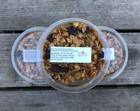 clear tubs of granola with oats, raisins, and pumpkin seeds