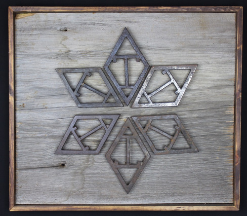 antique cast iron trivets displayed & mounted on circa 1870s barnboard