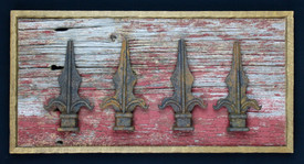 antique cast iron fence posts mounted on circa 1870s barnboard