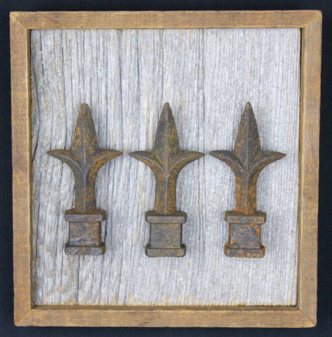vintage cast iron fence posts mounted on circa 1870s barnboard
