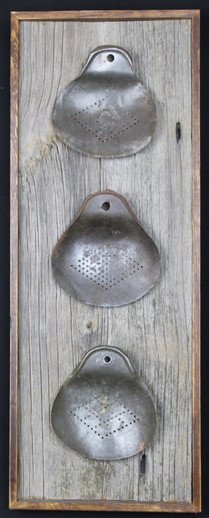 antique tin cream skimmers mounted on circa 1870s barnboard