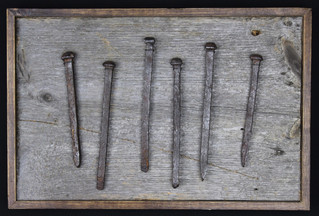 antique hand cast iron barn nails mounted on circa 1870s barnboard