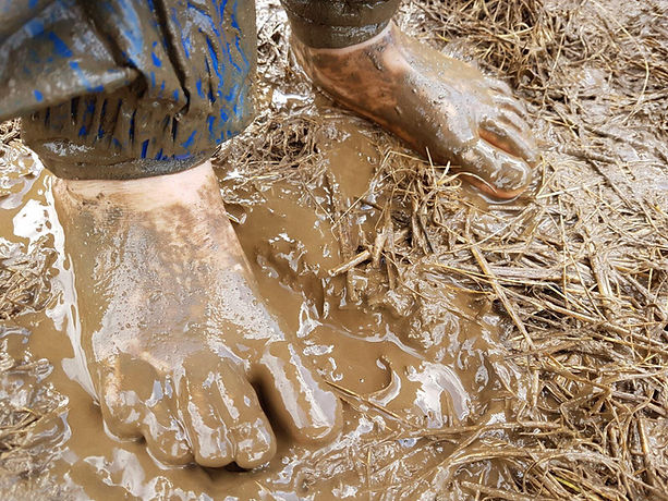 Child barefoot in the mud