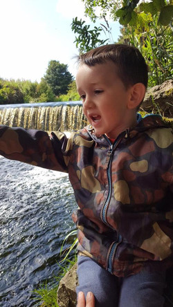 Child overlooking river at forest school
