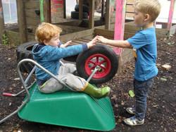 Boys use wheelbarrow in role play outdoors