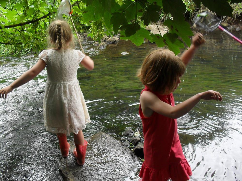 Children fishing in a river in West Lothian, Scotland