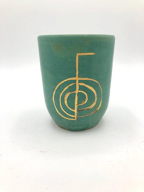 Beker met gouden reiki-symbool