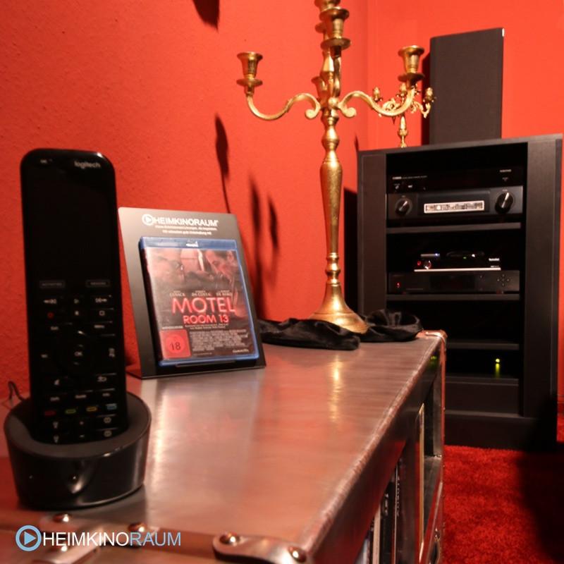 Universalfernbedienung Logitech Harmony und Technikschrank im Hintergrund
