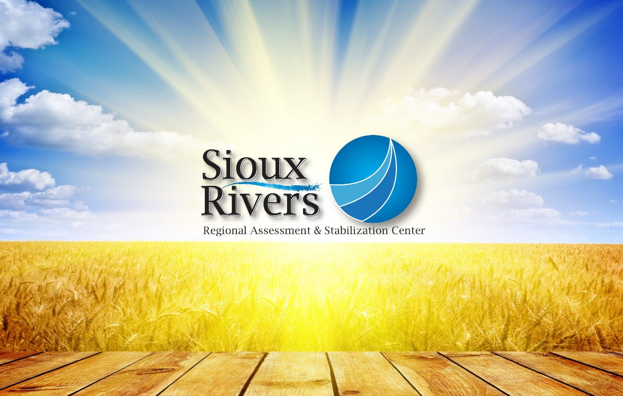 Landscape photo of field and sunburst sky with Sioux Rivers logo. Sioux Rivers Regional Assessment and Stabilization Center | Sioux, Lyon, Plymouth, O'Brien and Dickinson County, Iowa.