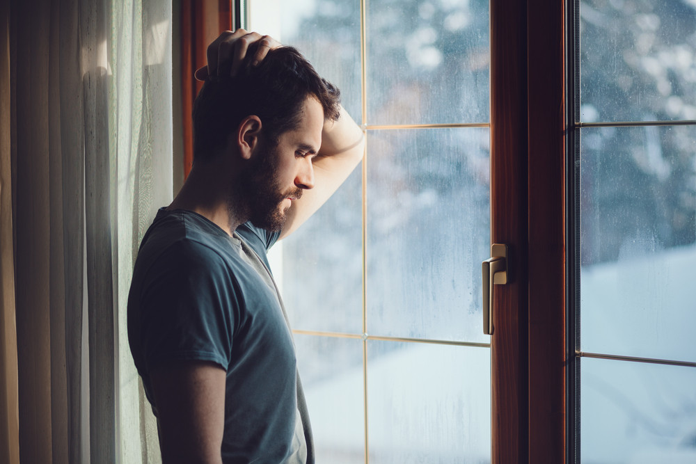 man standing by window sad