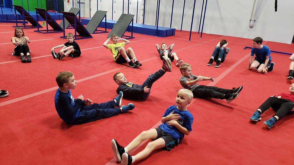Children practicing for the ninja obstacles by workikng on their core.