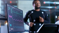 Close-up Shot of a Monitor With EKG Data. Male Athlete Runs on a Treadmill with Electrodes