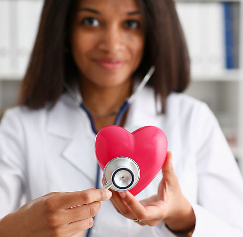 Beautiful black smiling female doctor hold in arms red toy heart closeup. Cardio therapeut