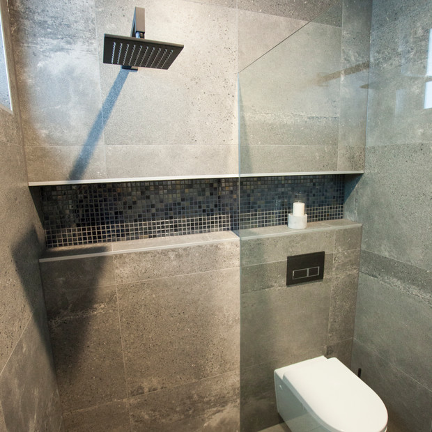 Modern floor to ceiling shiny brown tiles with toilet and shower head