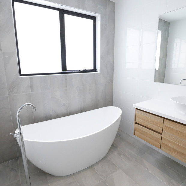 Modern Bathroom with single bath tub and floating benchtops