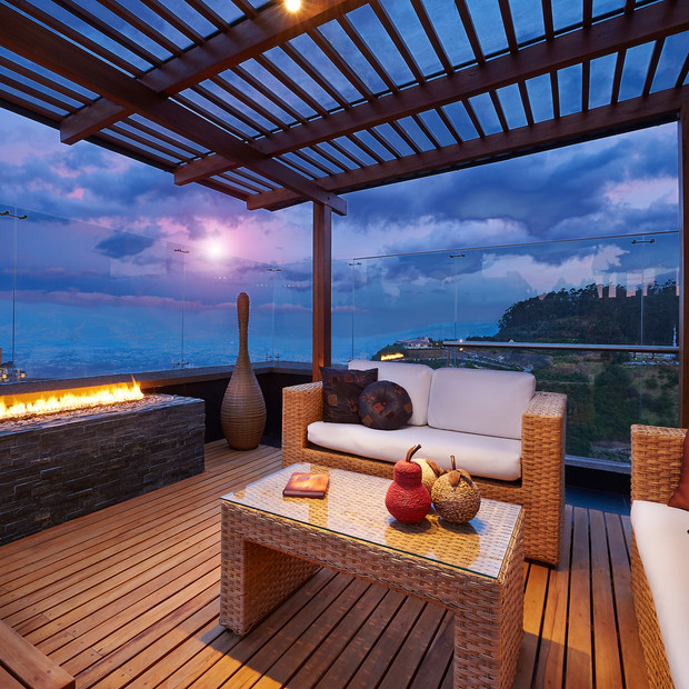Outside alfresco sitting area withoutdoor fireplace overlooking the ocean and louvers