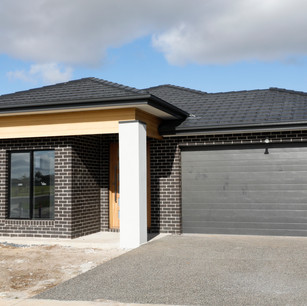 New modern home build with white facade and black roller door no landscaping