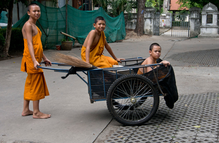 Buddhist novices cleaning a temple in Thailand