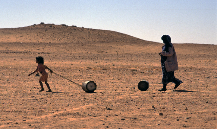 Saharawi mother and child from from Western Sahara, carry domestic fuel in a refugee camp in Algeria