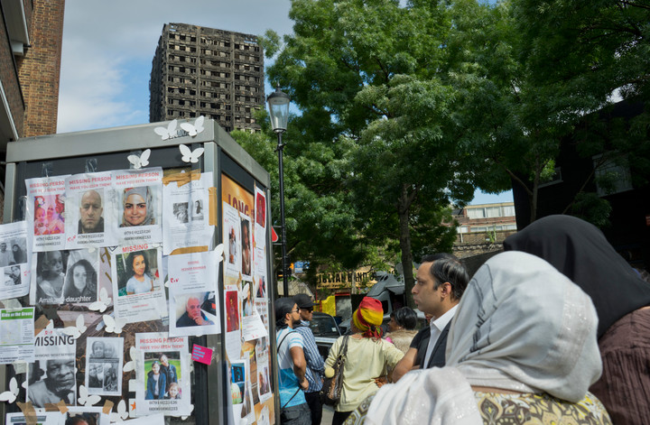 Local residents looking at photos of victims of the fire disaster at the Grenfell Tower