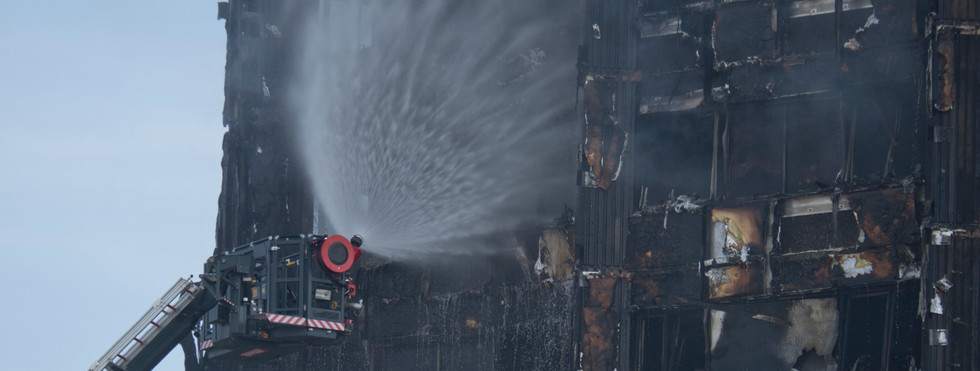 Fire fighters pouring water on to remnants of Grenfell Tower in London, UK
