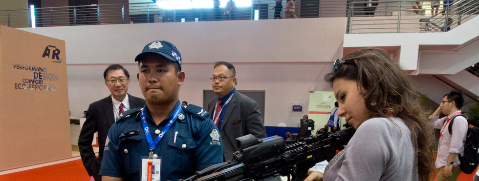 Young woman trying a machine gun at an arms fair in Singapore