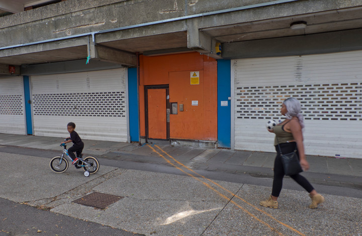 Mother and child walk past closed down shops in derelict council housing estate to be demolished to build new luxury housing blocks in London