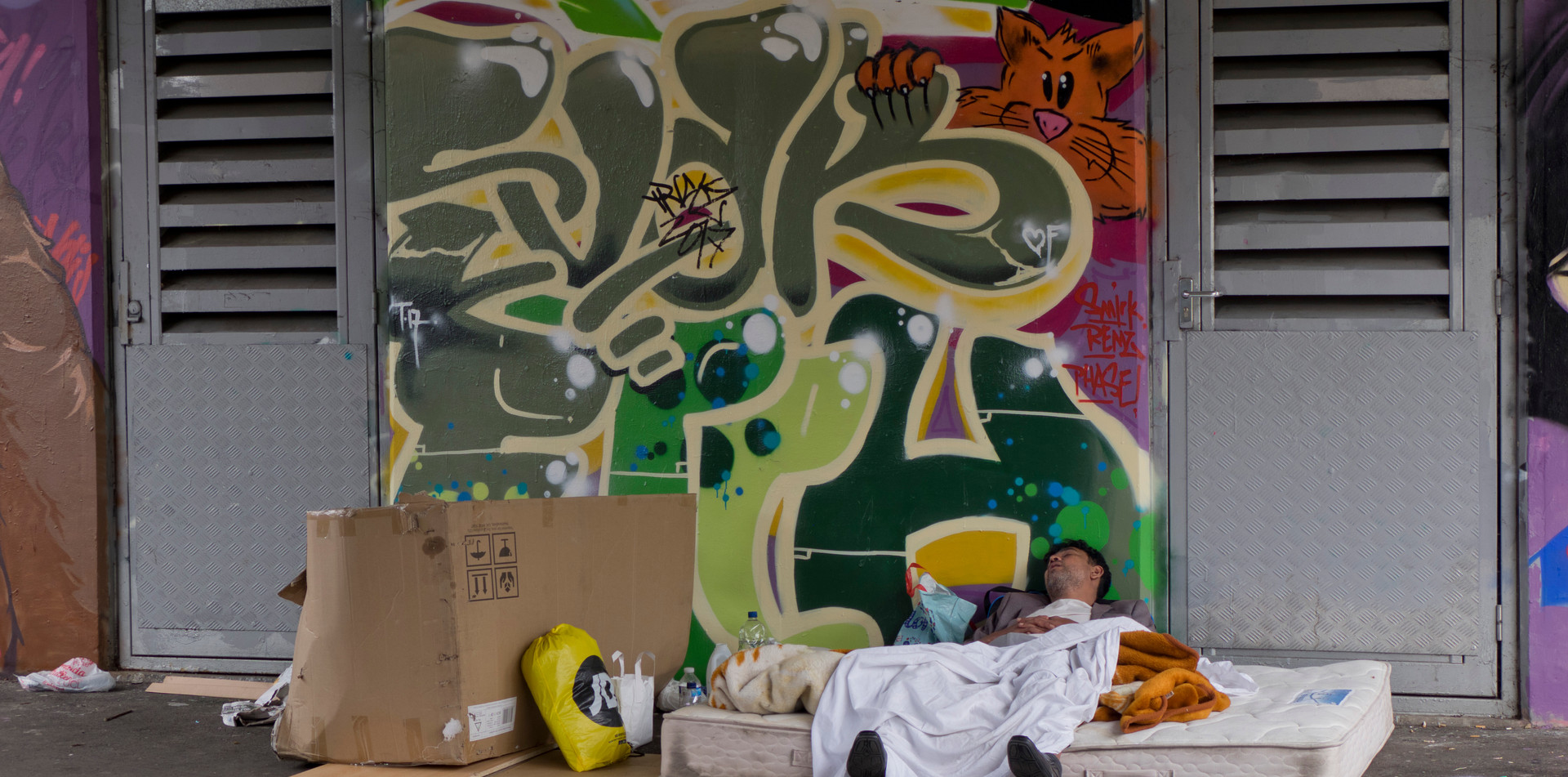 Young homeless man sleeping under railway bridge with graffiti art in London
