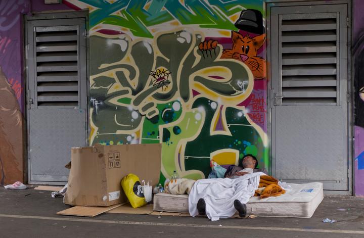Young homeless man sleeping under railway bridge with graffiti art in London