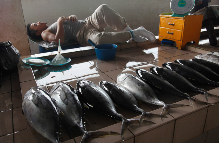 Tired fishmonger behind his stall in Malaysia