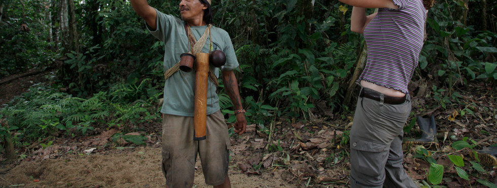 Huaorani first nation guide shows eco-tourist how to use a blow dart in the Yasuni reserve in Amazonian Ecuador