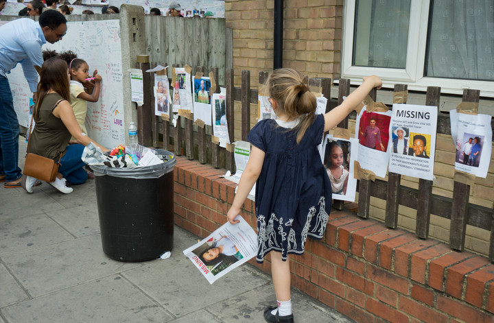 Visitors writing notes of condolence for victims of the fire disaster at the Grenfell Tower in London