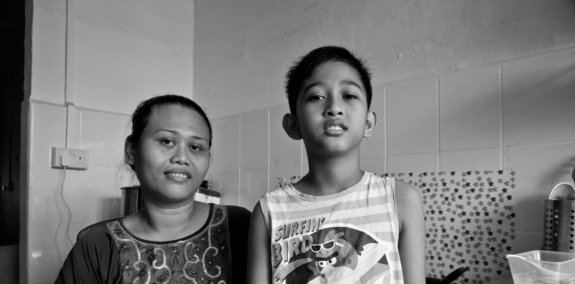 Single mother and son sharing a small new flat in Singapore