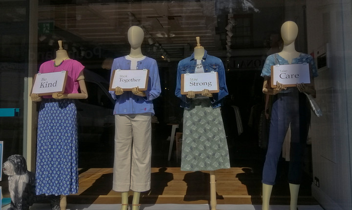 Mannequins at a closed-down women's clothes shop with messages of hope due to Coronavirus