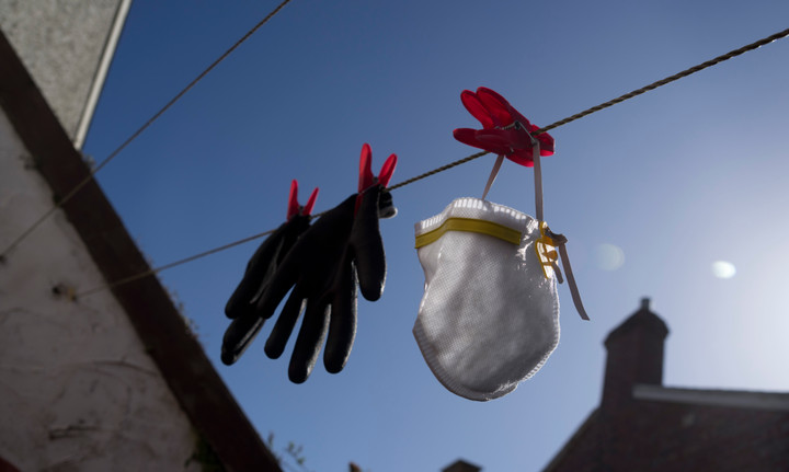 Face mask and protective gloves on a washing line