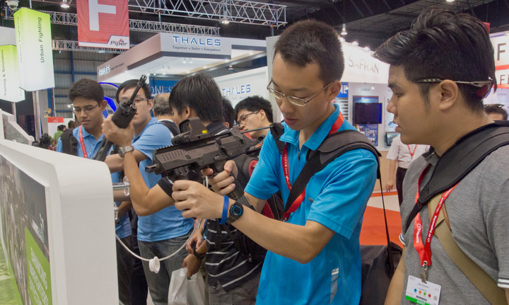 Young men trying machine guns at an arms fair in Singapore