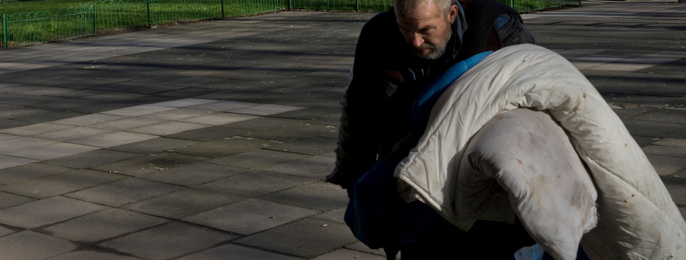 Homeless man with bedding looking for a place to sleep in a run-down local authority council housing estate in London