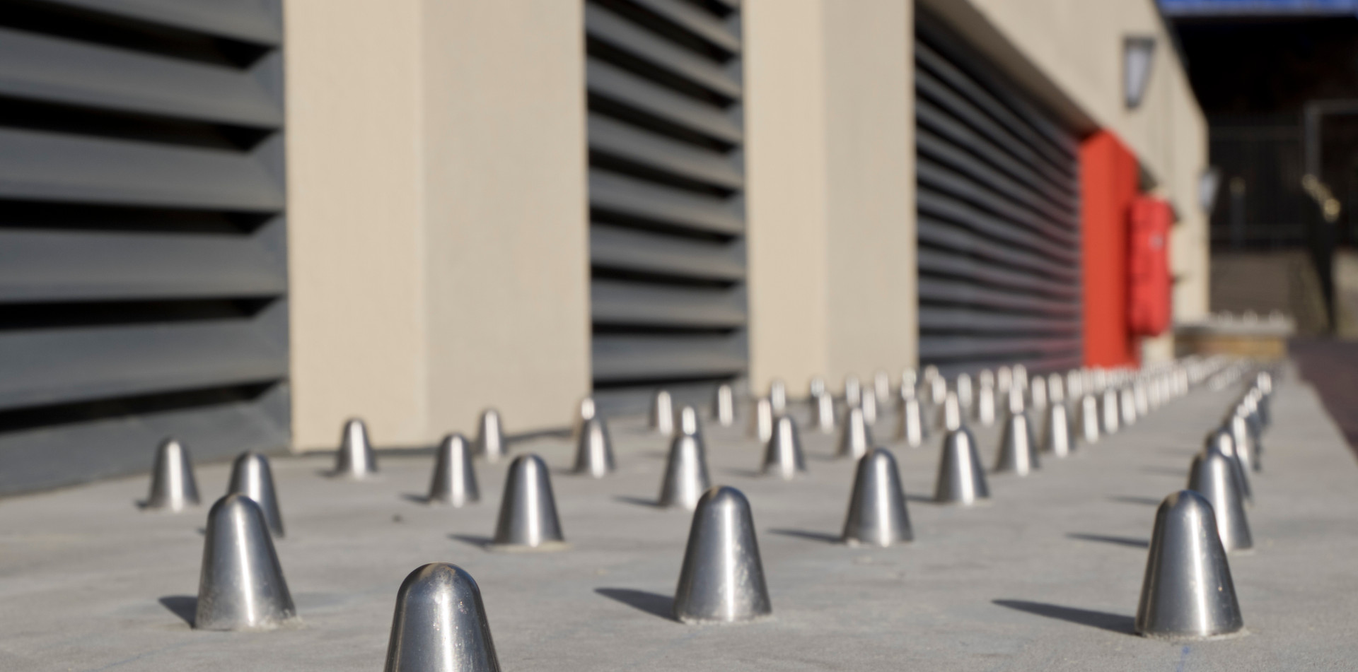 Anti-homeless spikes and rough surfaces installed in a luxury housing complex to deter homeless people from sleeping in the area around the Limehouse Basin marina in London