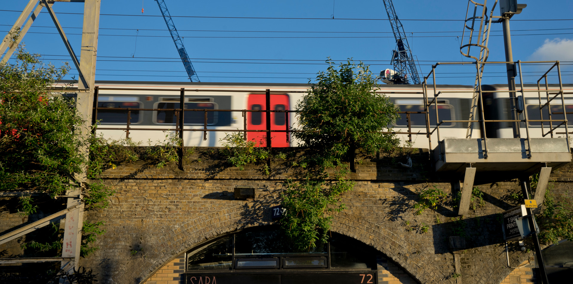 Small business under railway arches by train and overground station, to be redeveloped to build luxury housing and new fashionable shops in Hackney, London