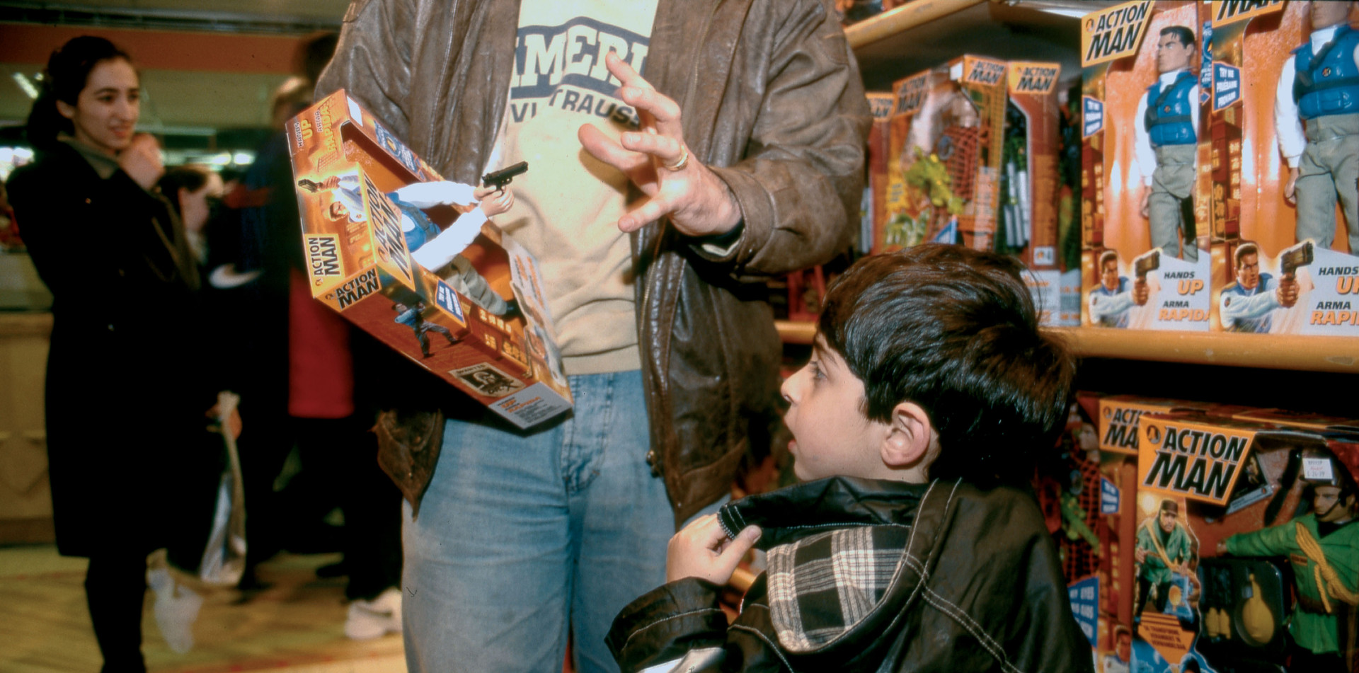 Father convincing son to take an Action Man toy gun